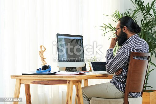 1098316816 istock photo Programmer by computer monitor 1098316684