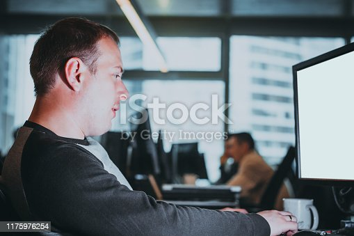 1170082011 istock photo Programmer concentrate on problem. Portrait of young man working in office on desktop computer and looking at monitor. Developing programming and website working in IT company office 1175976254