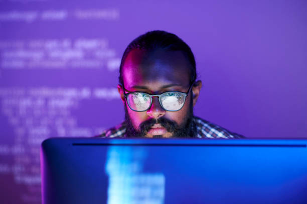 Programmer in front of monitor Young serious programmer in eyeglasses concentrating on working with coded data on computer screen java programming language stock pictures, royalty-free photos & images