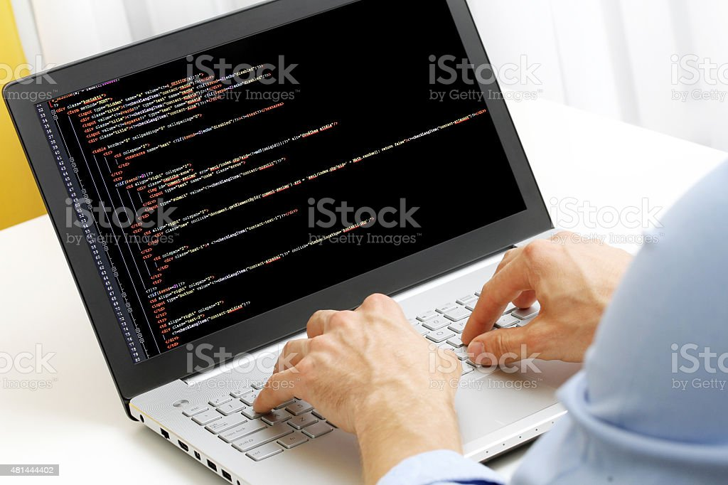 programmer profession - man writing programming code on laptop stock photo