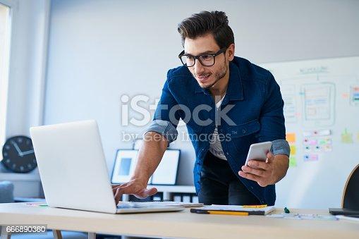 istock Programmer, web developer, designer working at office comparing mobile and desktop website versions 666890360