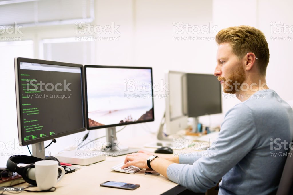 Programmer working in a software developing company office stock photo