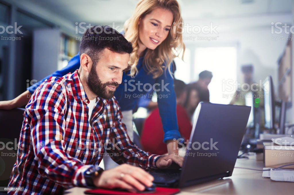 Programmer working in a software developing company office Programmer working in a software developing company office Computer Programmer Stock Photo