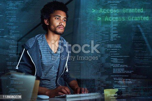 Shot of a young programmer working on computer code at night