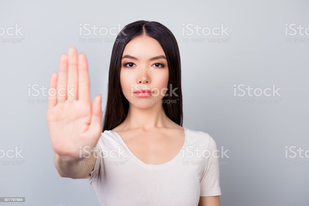 Prohibition symbol. Closeup portrait of young, serious, pretty girl making stop sign with her hand  on grey background stock photo