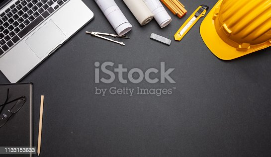 istock Project blueprints, yellow hard hat and computer laptop on black color, top view 1133153633