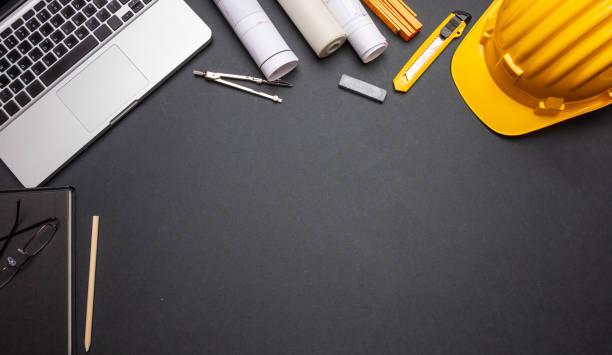 projektpläne, gelber harter hut und computer-laptop auf schwarzer farbe, obere ansicht - renovierung konzepte stock-fotos und bilder