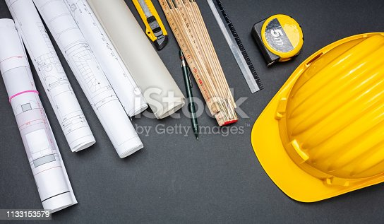 istock Project blueprints, yellow hardhat and engineering tools on black 1133153579