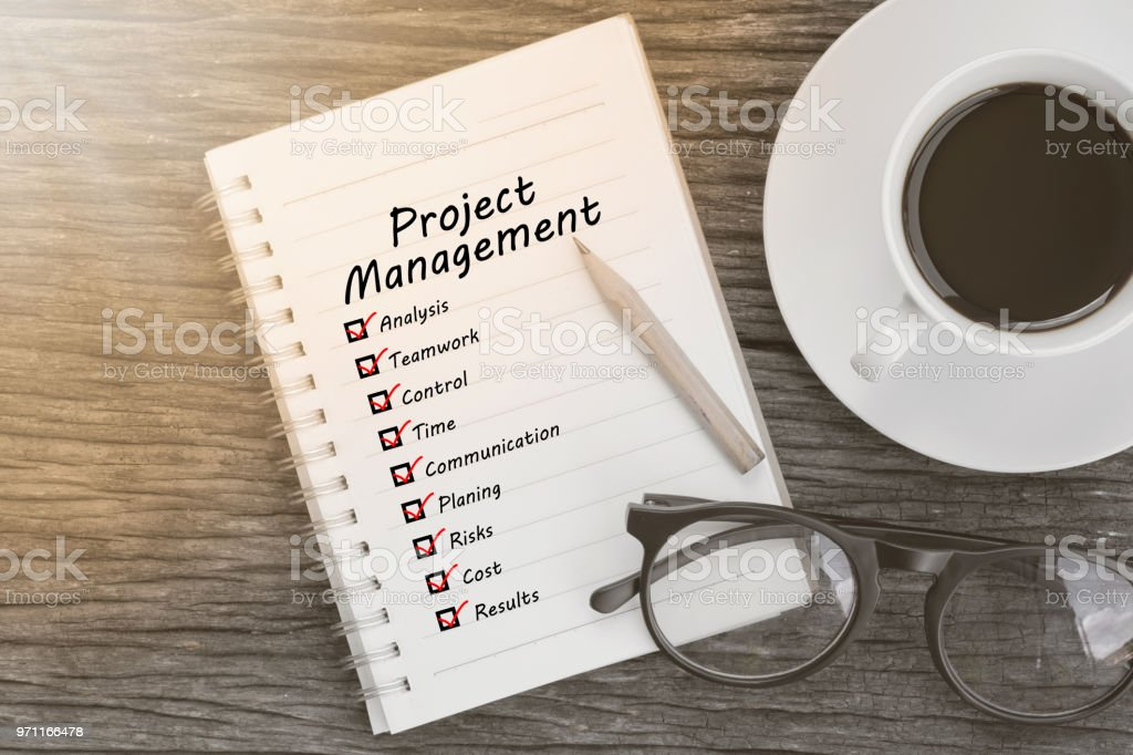 Project management and check list marks in notebook with glasses, pencil and coffee cup on wooden table. Project management concept. stock photo