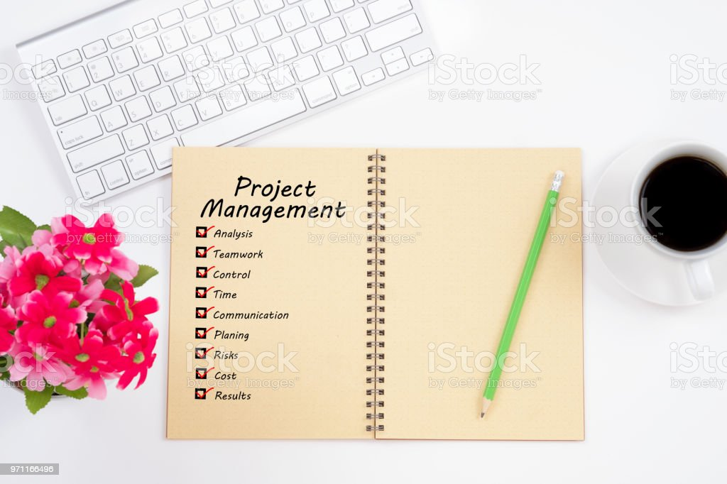 Project management and check list marks in notebook with keyboard, pencil and coffee cup on white table. Project management concept. stock photo