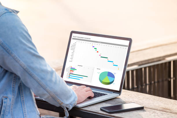 Project management dashboard concept. A man is working using laptop doing project management dashboard on screen. stock photo