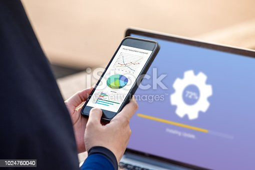 istock Project management dashboard concept. Hijab woman holding phone with management project dashboard on screen with installing update on screen laptop background. 1024760040