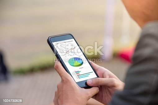 istock Project management dashboard concept. Man holding phone with management project dashboard on screen. 1024730528