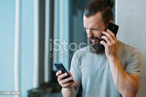 istock project management sceptic man smartphones 1158716725