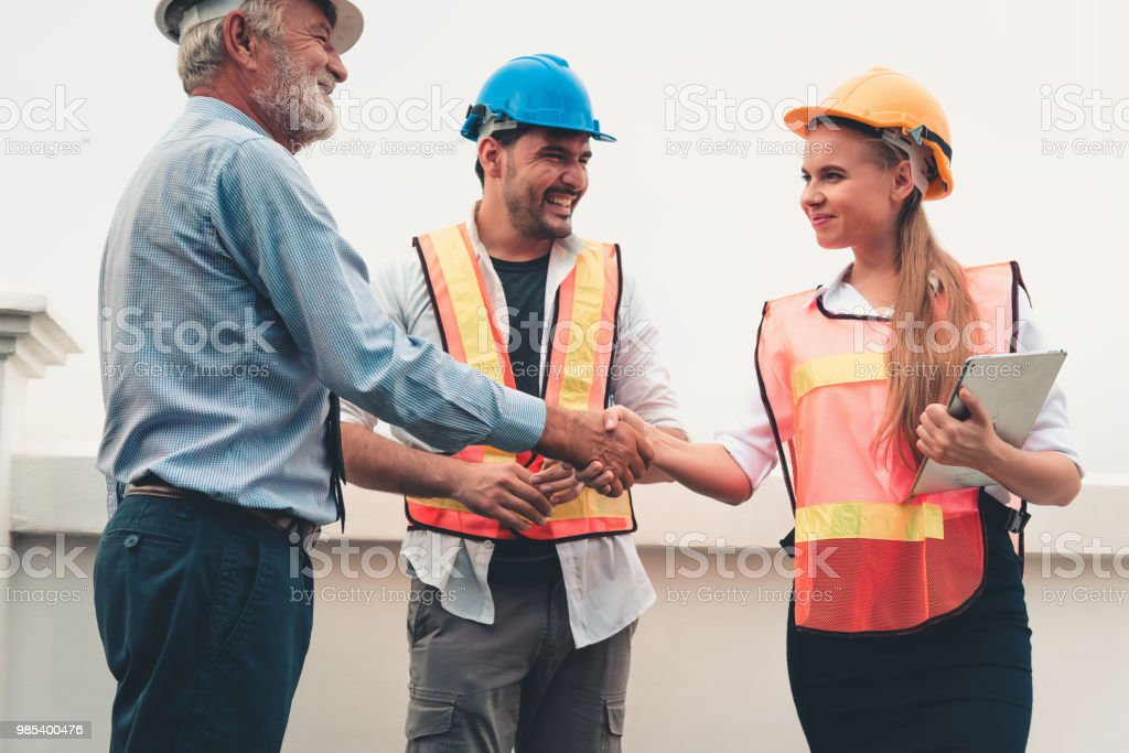 Project management team of engineers and architects are handshake together after dealing their project, Business construction concepts royalty-free stock photo