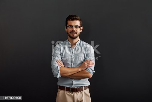 612752180istockphoto Project manager. Confident and young bearded man looking at camera with smile and keeping arms crossed while standing against dark background 1167909406