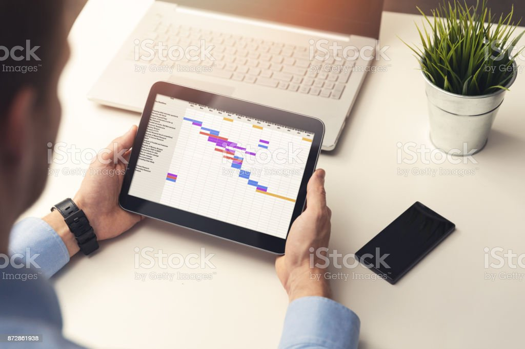 project manager looking at gantt chart on digital tablet in office project manager looking at gantt chart on digital tablet in office Adult Stock Photo