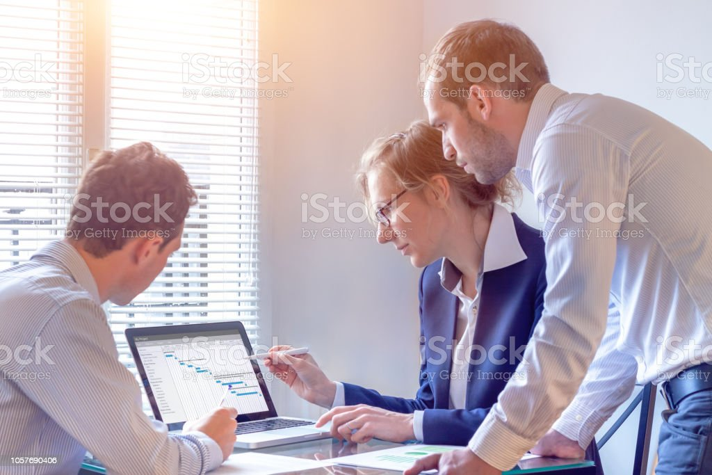 Project manager meeting with team for decision on planning milestones and deliverables, Gantt chart schedule on computer screen, 3 people in office stock photo