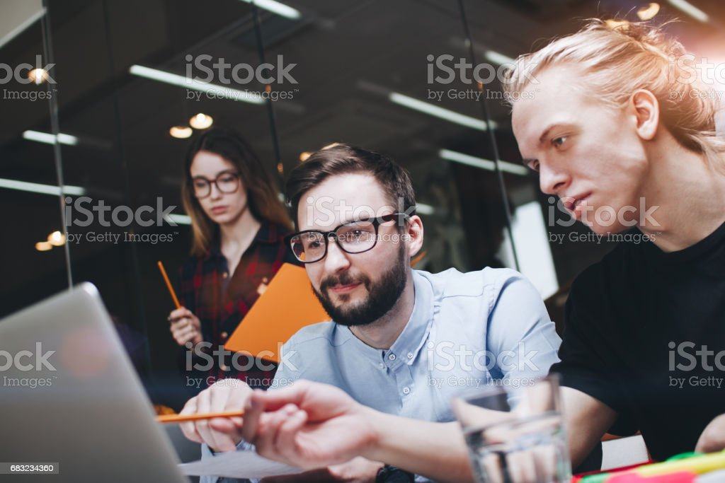研究過程的專案經理。Coworking 團隊對新斯特一起工作。友誼創造力的年輕人和使用現代筆記本電腦和文書工作 免版稅 stock photo