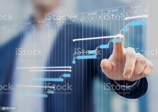Project Manager Updating Gantt Chart Planning On A Virtual Screen Stock Photo - Download Image Now