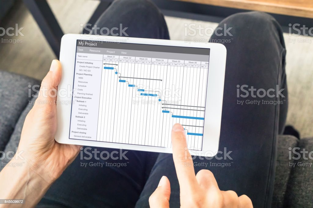Project manager updating Gantt chart schedule, planning software, tablet computer stock photo