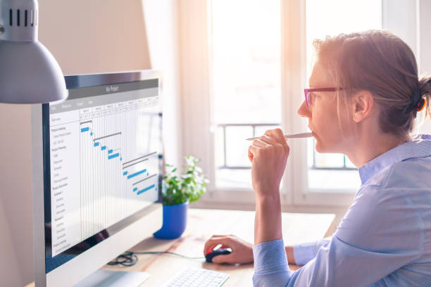 Project manager using Gantt chart, tasks planning and scheduling, computer stock photo