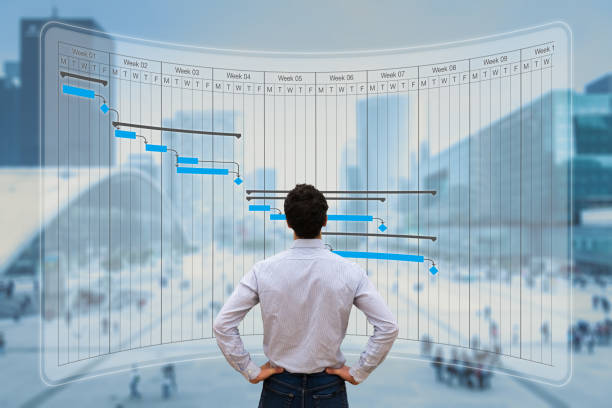 Project manager working with Gantt chart planning, tracking milestone and deliverables and updating tasks progress, scheduling skills, on virtual screen with city background stock photo