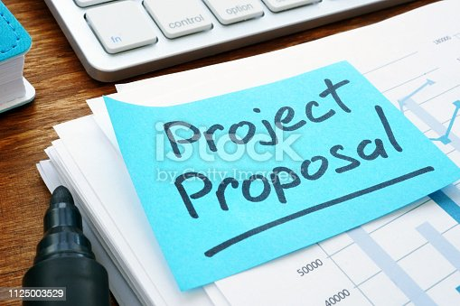 Project Proposal with stack of documents and keyboard.
