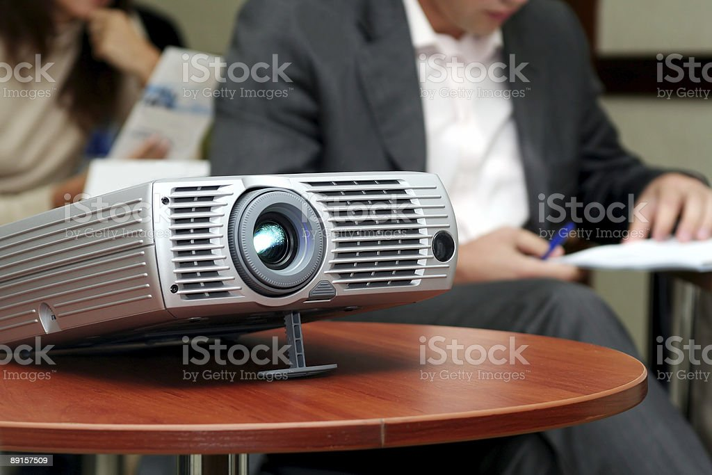 Projector on table with two person behind (horizontal) stock photo