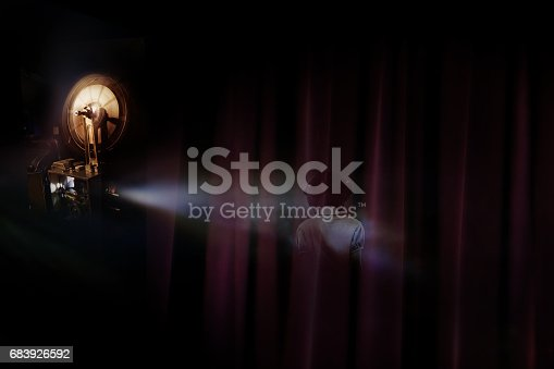 istock projector shows the horror film, kid ghost in the darkness. 683926592