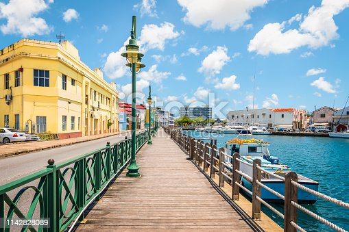 Bright image of wooden promenade at the waterfront of Bridgetown in Barbados. Colorful building against blue sky with white clouds. Boats and yachts in the harbor.