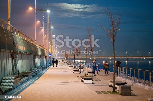 Riga, Latvia – January 6, 2019: Promenade of the river Daugava on an autumn evening. People can be seen walking in the distance.