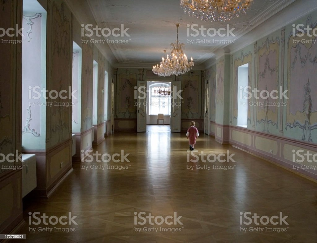 Promenade through royal interior Little girl all alone in a big palace hall. Architecture Stock Photo