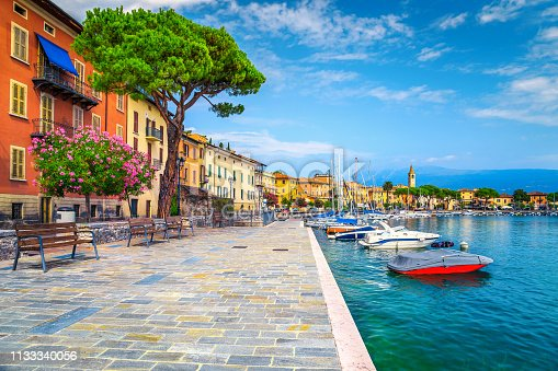 Wonderful paved walkway with colorful mediterranean flowers. Luxury yachts, boats and sailing boats in the majestic harbor of Toscolano-Maderno, lake Garda, Lombardy region, Italy, Europe