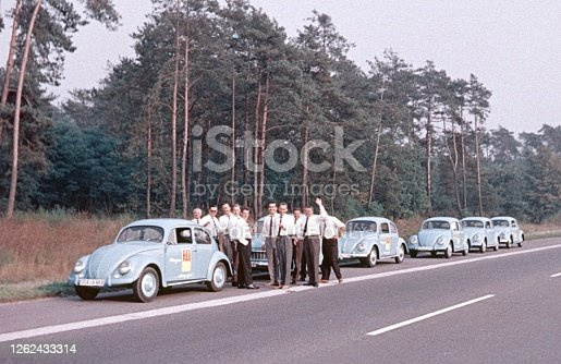 Hesse, Germany, 1964. Sales representatives on a promotion tour with a vehicle column take a break from driving on the roadside of a motorway.