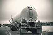 A propane delivery truck is driving down a highway in springtime.  The truck has the required 1075 2 placards indicating that the vehicle is transporting propane -  flammable gas - class 2.  The placards alert any emergency responders to vital hazard information.