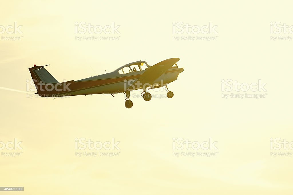Propeller airplane flying against the sun royalty-free stock photo
