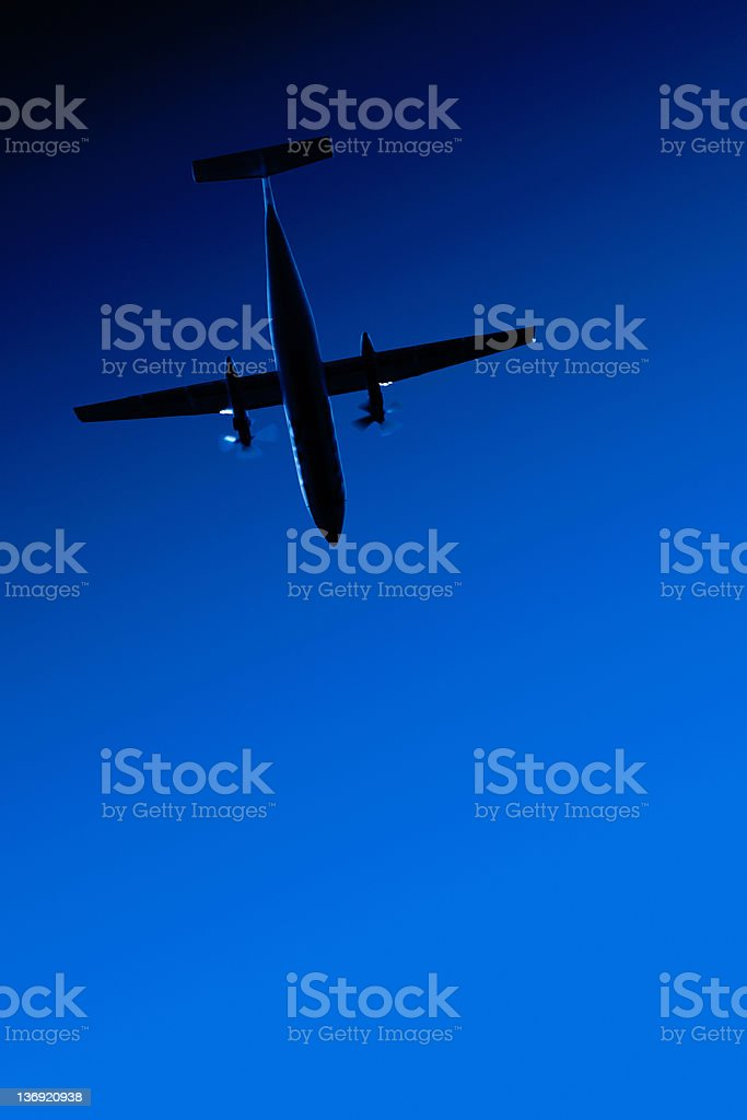 XL propeller airplane flying at night royalty-free stock photo