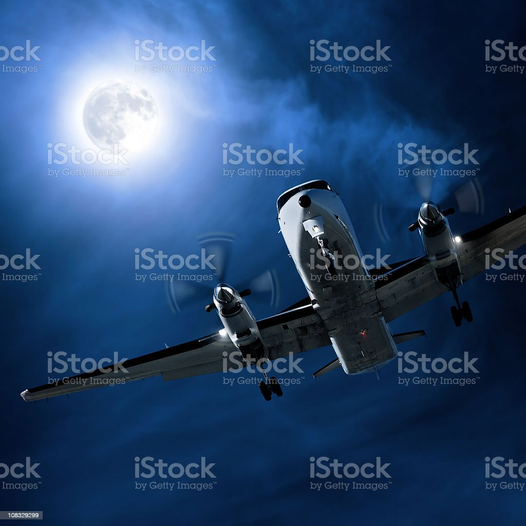 propeller airplane landing at night royalty-free stock photo