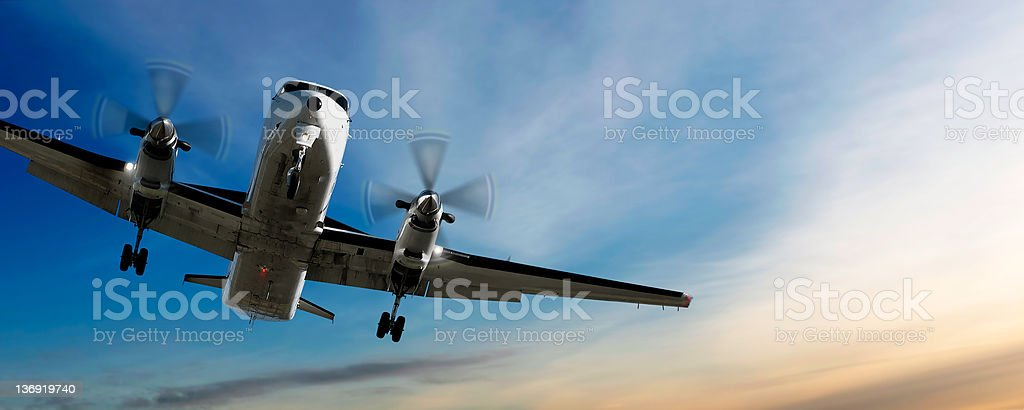 propeller airplane landing at sunset stock photo