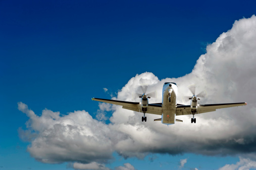 XL propeller airplane landing in cloudy sky