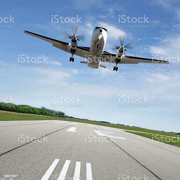 Photo of XL propeller airplane landing on runway