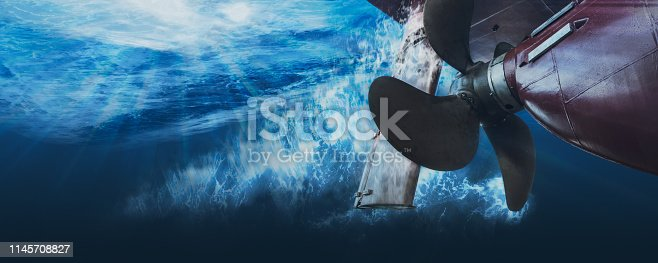 Propeller and rudder of big ship underway view from underwater. Close up image detail of ship. Transportation industry. Freight transportation. Ship repair, underwater survey and shipping business concept.