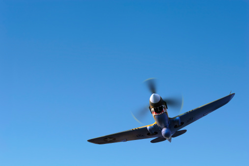 propeller fighter airplane flying in clear sky