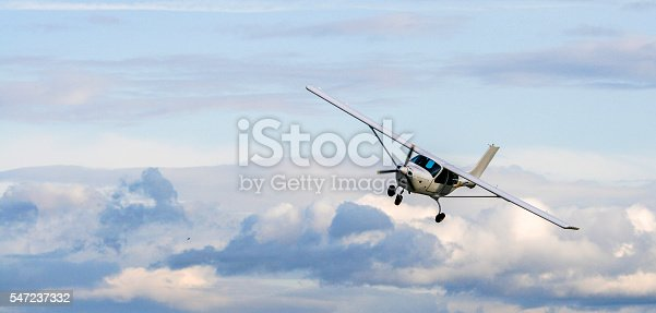 Propeller plane flying on the cloudy sky background