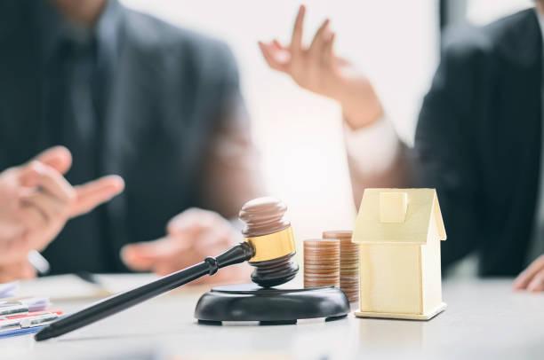 Subasta de propiedades, Gavel de madera y casa modelo sobre fondo de mesa blanco con imagen borrosa de fondo de empresarios. - foto de stock