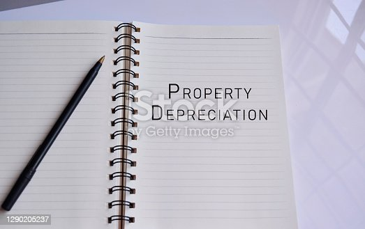 Property depreciation text on a notepad with reflection of window glass