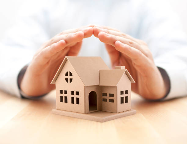 Property insurance. House miniature covered by hands. stock photo