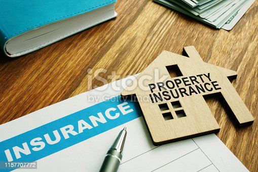 istock Property insurance stamp on a model wooden home. 1157707772