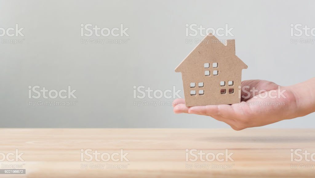 Property investment and house mortgage financial concept, Hand holding wooden home stock photo